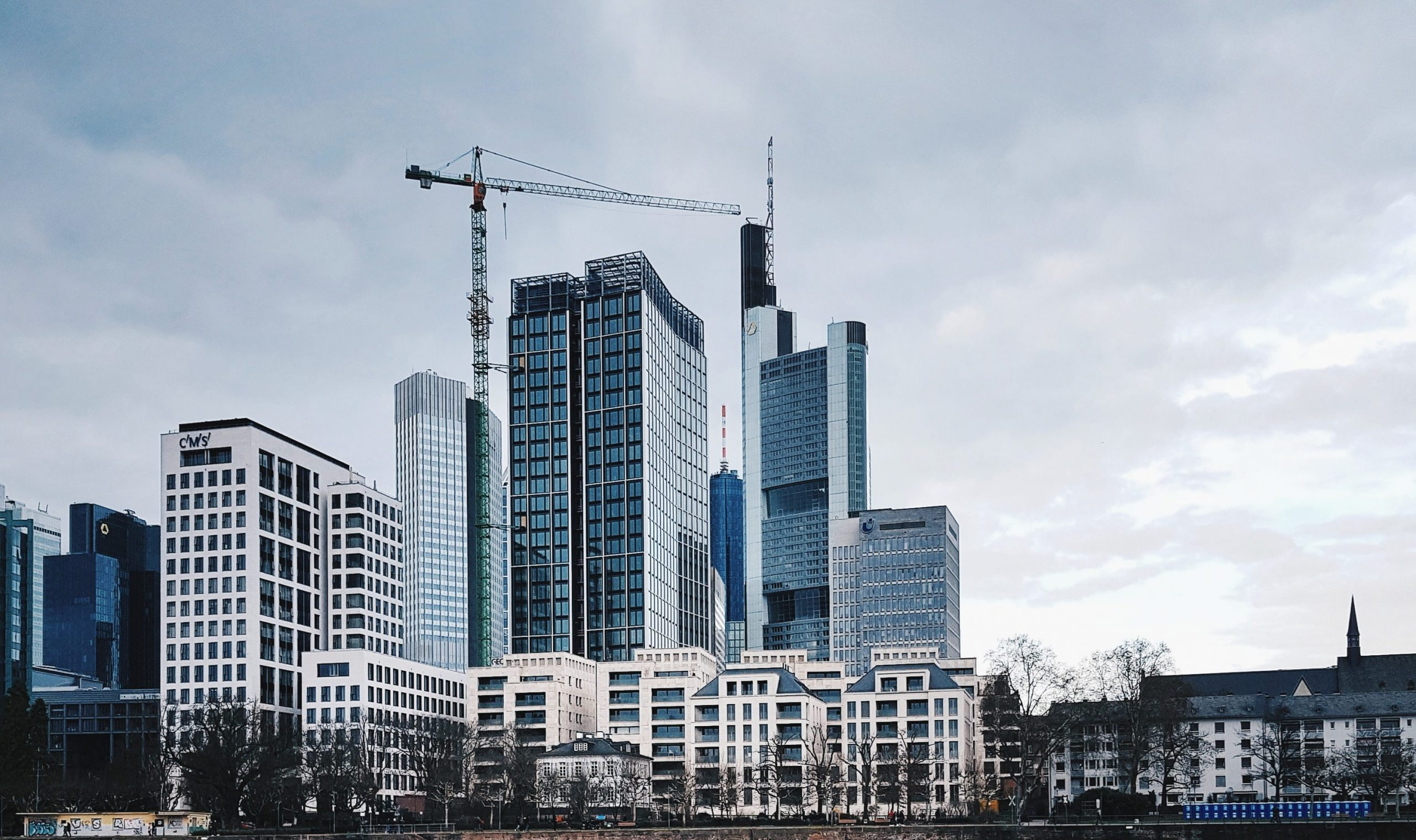 urban office towers with a crane under a cloudy sky